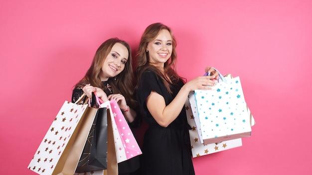 バッグの多いスタジオでカメラにポーズをとる2人の若い女性