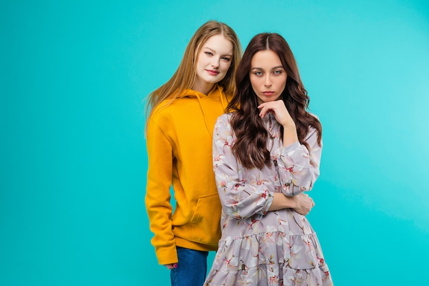 Two young women posing  isolated over bright blue turquoise background