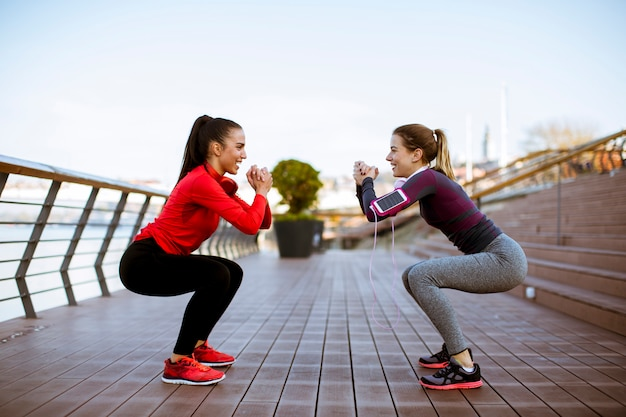 Two young women practice stretching outdoor