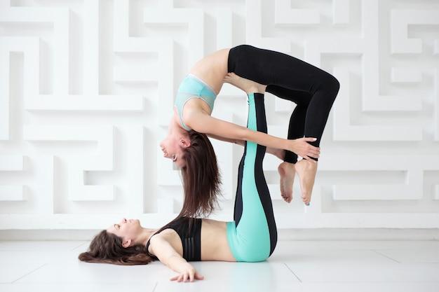Две молодые женщины, практикующие равновесие позы акро-йоги