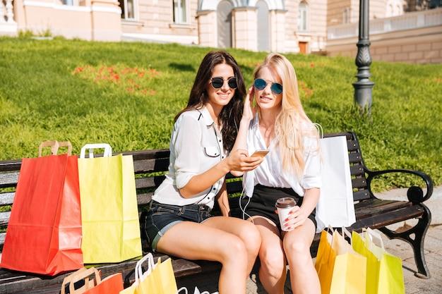Две молодые женщины отдыхают на скамейке и слушают музыку в наушниках после покупок