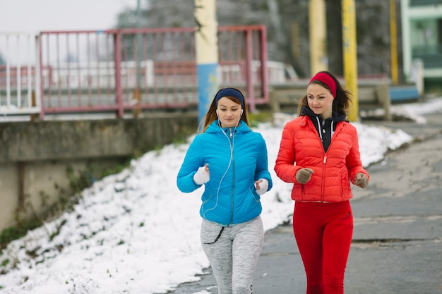 Two young women running on street in winter
