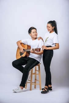 Two young women sat on a chair and played guitar.