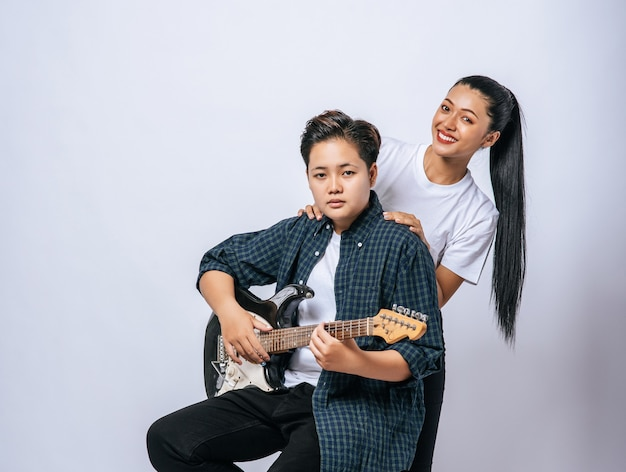 Две молодые женщины сидели на стуле и играли на гитаре.