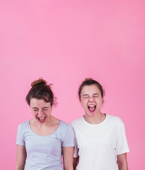 Two young women screaming against pink background