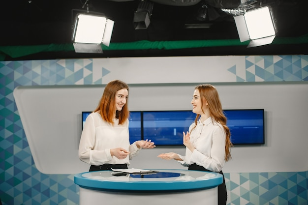 Two young women on set for tv interview, focus on women. tv studio.
