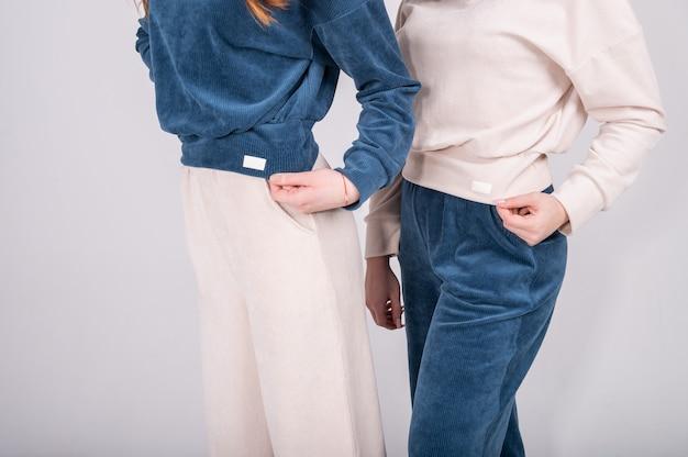Две молодые девушки демонстрируют одежду, вязаные костюмы из натуральной ткани, модную повседневную одежду.