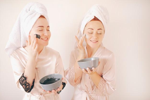 흰 배경에 고립 된 그들의 머리에 수건 목욕 가운에 두 젊은 여성 자매. 집에서 스파. 그들은 얼굴에 피부 관리를위한 마스크를 만듭니다. 그리고 얼굴의 피부에 적용