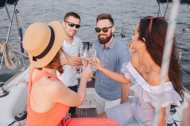 Две молодые женщины сидят и смотрят на мужчин. все они держат бокалы для шампанского. они смотрят друг на друга и улыбаются. люди ура.