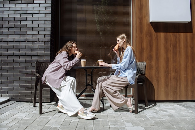 Two young women sit in a cafe eating and chatting while having fun together