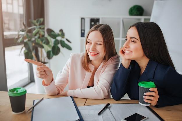 두 젊은 여성이 함께 회의실 테이블에 앉아. 손가락과 웃음으로 하나의 모델 포인트. 그녀의 친구는 커피 한 잔을 들고 왼쪽을 본다. 그녀도 웃고있다.