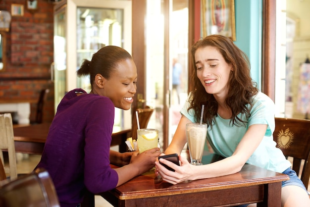 Two young women sitting at cafe with mobile phone