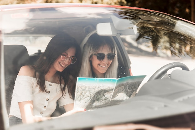 Two young women sitting in car looking at map