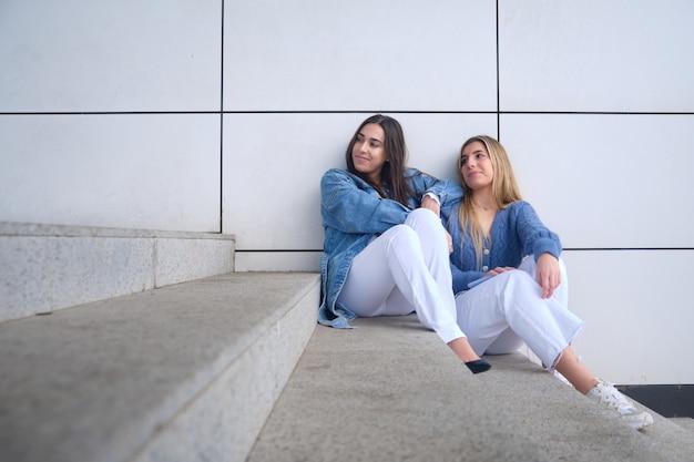 通りに座っている2人の若い女性。金髪とブルネット。彼らは同じ方向を向いています。白い壁。コピースペース