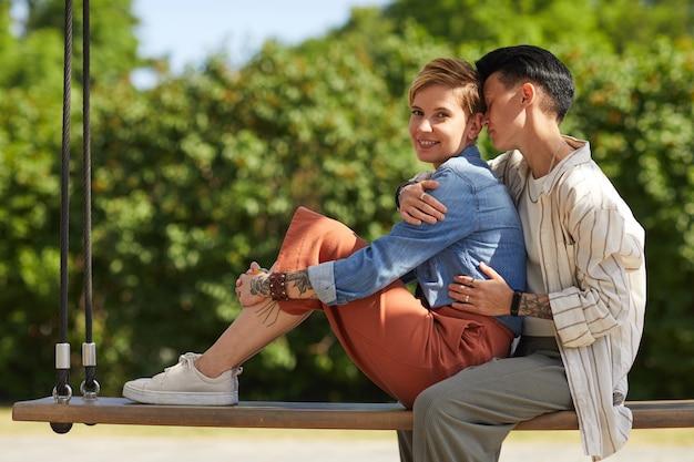 屋外でブランコに座って抱き合って楽しんでいる2人の若い女性