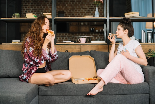 Two young women sitting on sofa eating pizza