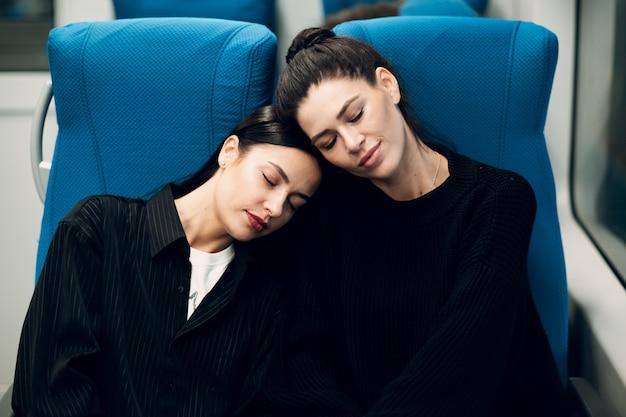 電車で寝ている2人の若い女性