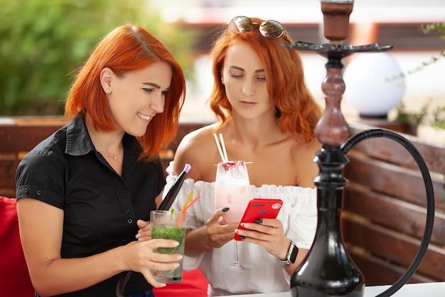 두 젊은 여성이 물 담뱃대를 피우고 길거리 카페에서 칵테일을 즐깁니다.