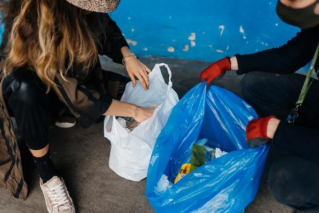 ごみを分別する2人の若い女性。リサイクルの概念。廃棄物ゼロ