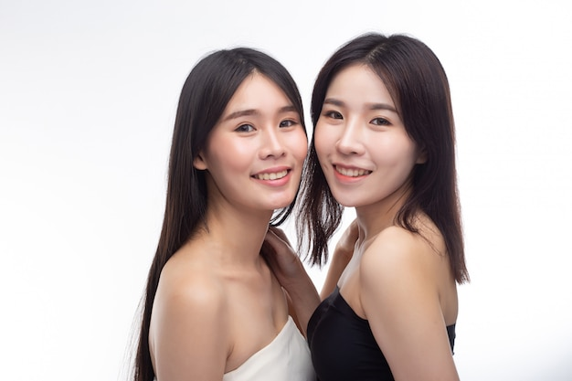 Two young women stand happily facing each other.