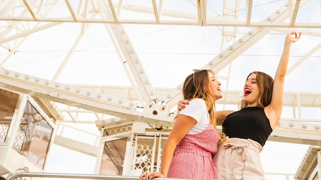 Two young women standing in front of ferris wheel making fun