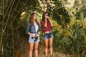 Two young women standing in forest clicking photograph with camera