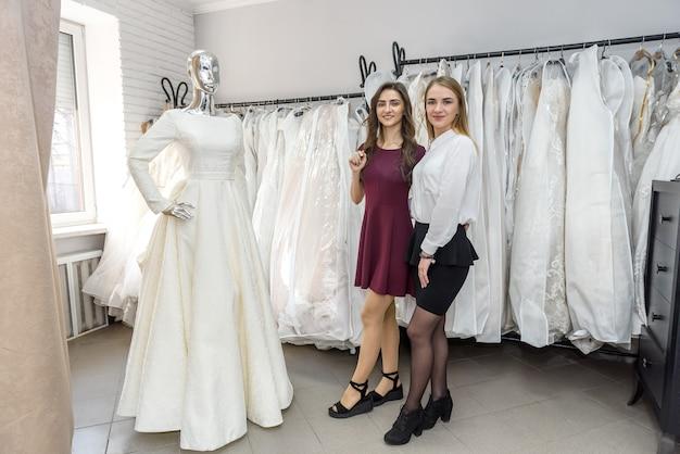 Две молодые женщины, стоящие возле манекена в свадебном салоне