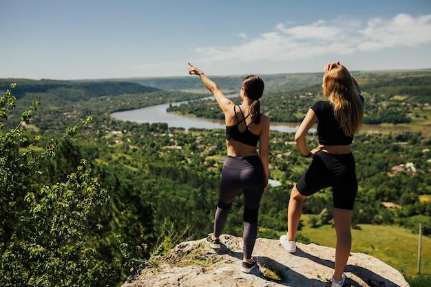 山の岩の上に立って美しい景色を見ている2人の若い女性