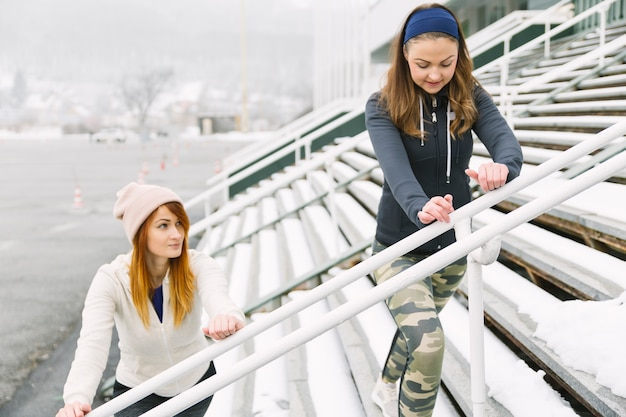 Two young women stretching on bleacher in winter