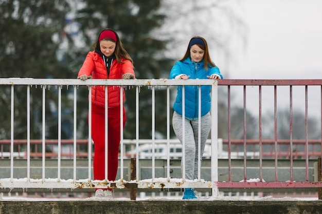 Two young women stretching near the railing