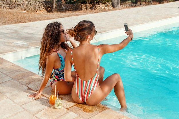 Two young women in swimsuits taking selfie with a phone and drinking tropical cocktails in the swimming pool