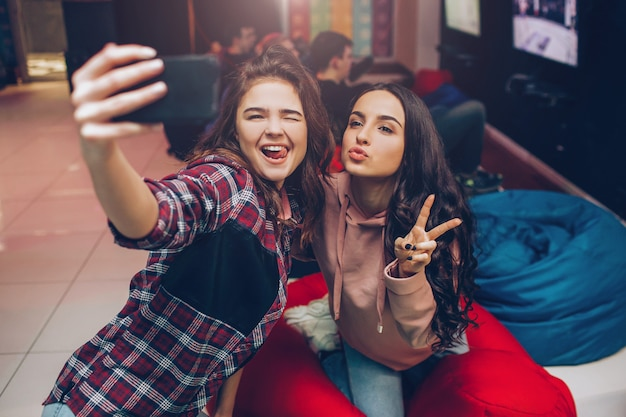 Two young women taking selfie on phone camera and posing in playing room. they shink and show fingers. cheerful models smile.