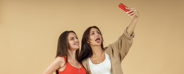 Two young women taking selfie on smartphone and stick tongue out on beige background