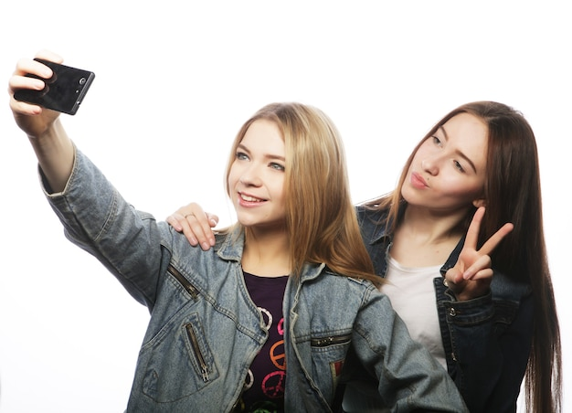Two young women taking selfie with mobile phone, isolated on white