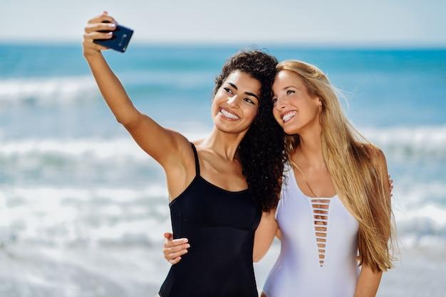 Due giovani donne che assumono selfie con smart phone in costumi da bagno su una spiaggia tropicale.