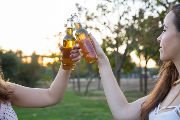 Two young women toasting with beer bottles having fun in park