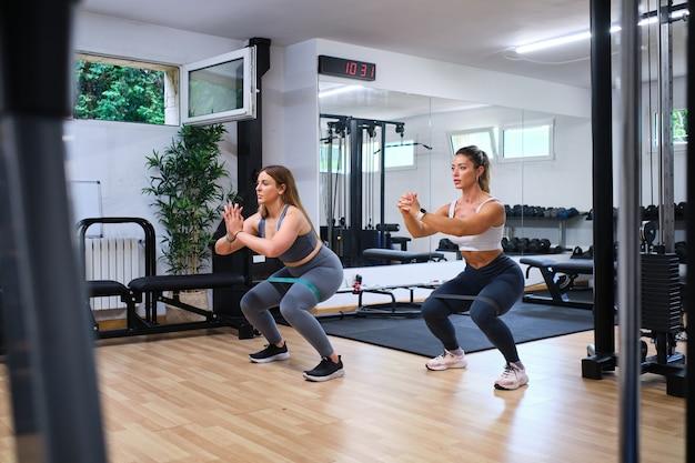 ジムでゴムバンドで臀筋をトレーニングする2人の若い女性