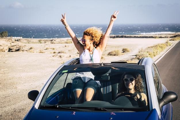 컨버터블 자동차를 타고 여행하는 두 명의 젊은 여성이 즐거운 시간을 보내고 있습니다. 친구가 도로에서 차를 운전하는 동안 v 표시와 함께 포즈를 취하는 젊은 여자. 자동차 여행을 즐기는 두 여자 친구