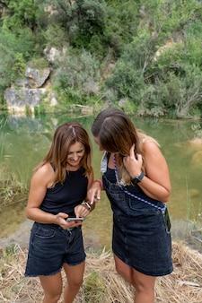携帯電話を使用して2人の若い女性。