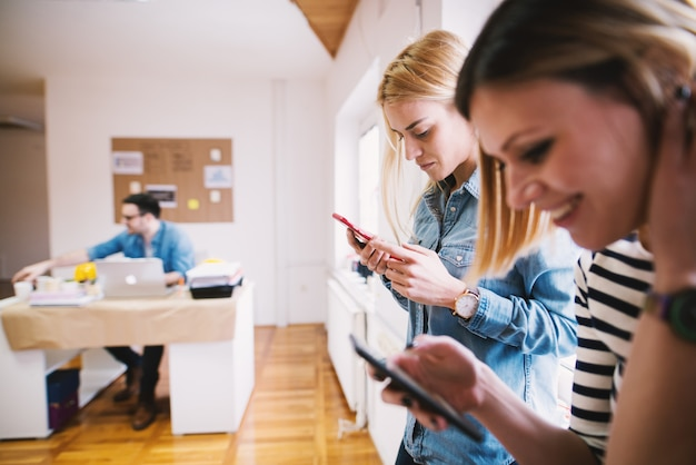 明るいオフィスでの休憩にモバイルを使用している2人の若い女性。 Premium写真