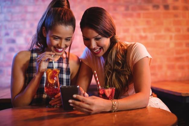 携帯電話を使用して2人の若い女性