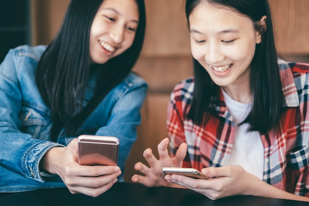Two young women using mobile phones.