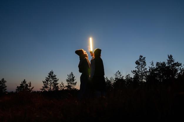 황혼에 사진 세션을 위해 led 램프와 함께 추운 가을 밤에 시골에서 걷는 두 젊은 여성