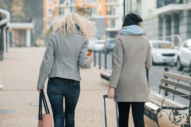 Two young women in warm clothes walking with travel suitcase
