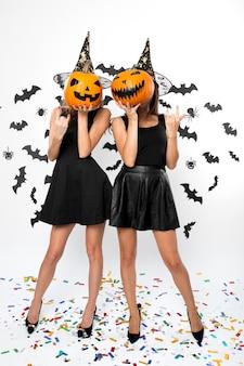 검은 드레스, 마녀 모자, 하이힐을 입은 두 명의 젊은 여성이 할로윈 호박을 얼굴에 붙이고 있습니다.