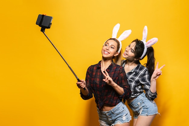 Two young women wearing cute easter rabbit ears and making selfie using stick
