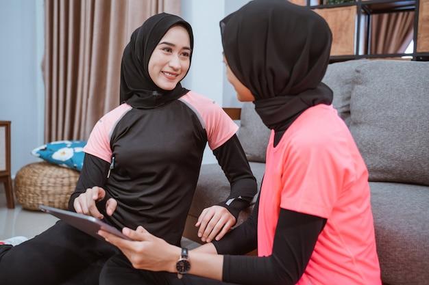 Две молодые женщины в спортивной одежде хиджаба улыбаются, отдыхая на полу, используя цифровой планшет, опираясь на диван дома