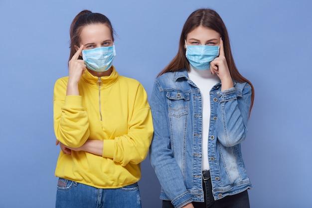 コロナウイルス病の保護マスクを身に着けている2人の若い女性