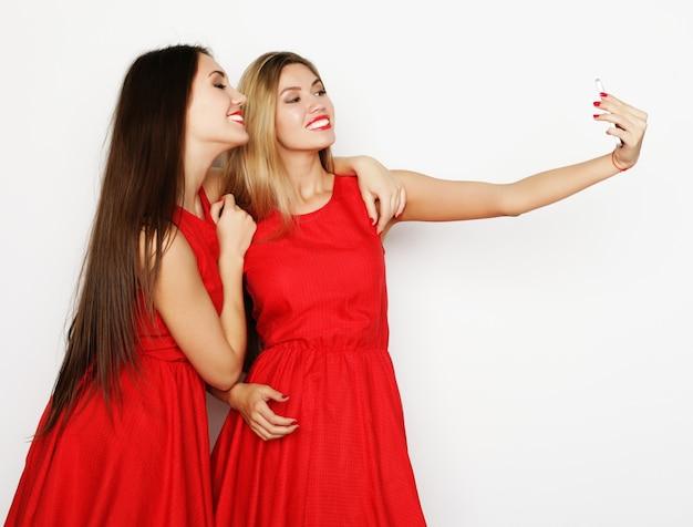 携帯電話で自分撮りをしている赤いドレスを着ている2人の若い女性