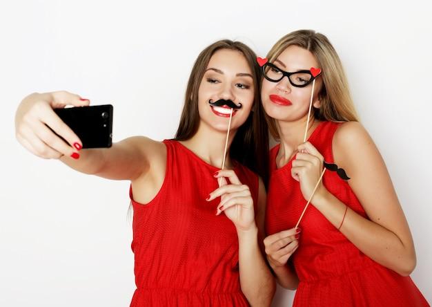 휴대 전화로 셀카를 찍는 빨간 드레스를 입고 두 젊은 여성